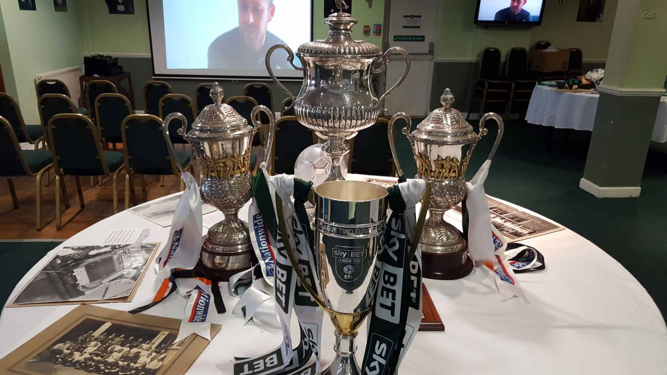 The 2016-17 League Two Runners Up Trophy with the 2001-02 and 2003-04 Winners' Trophy to the Left and right. Behind is the Stanley Spooner Memorial Cup, a Devon F.A. trophy.